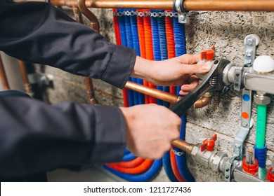 hands of plumber working in boiler room