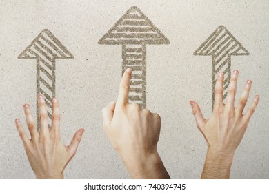 Hands pointing at drawn arrows on concrete background. Different direction concept