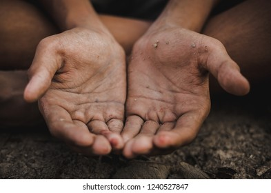 hands poor child or beggar begging you for help sitting at dirty slum. concept for poverty or hunger people,human rights,donate and charity for  underprivileged children  in third world