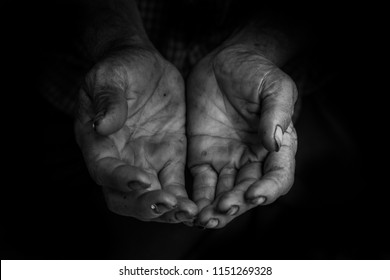 hands poor old man or beggar begging you for help sitting at dirty slum. concept for poverty or hunger people,human Rights,donate and charity,background text.low key tone,black and white.