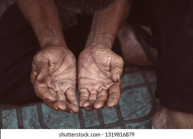 hands poor old man or beggar begging you for help sitting at dirty slum. concept for poverty or hunger people,human Rights,donate and charity,background text