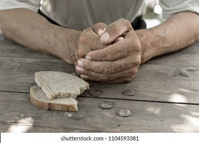 Hands the poor old man's, piece of bread and change, pennies on wood background. The concept of hunger or poverty. Selective focus. Poverty in retirement.Homeless.