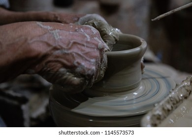 hands of a potter, creating a clay pot