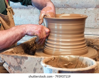 Hands of a Potter make a pot on a pottery wheel.