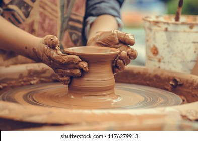 Hands of a potter. Potter making ceramic mug on the pottery wheel