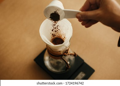 Hands pouring grounded coffee in filter. Preparing for alternative coffee brewing v60. Person holding spoon with grind coffee on background of glass kettle with pour over on scale