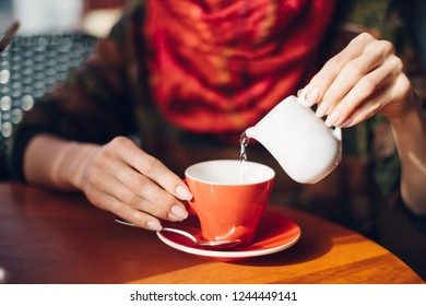 Woman's hands pouring hot water in red coffee cup - woman sitting in cafe with soft drink