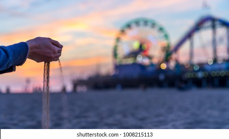 Hands pouring sand and the beach, Ferris Wheel in the background.