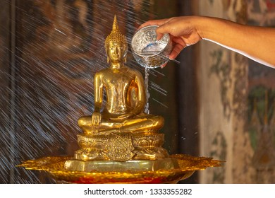 Hands pouring water on the Buddha statue Is an activity that Thai people perform on Songkran Day or the Thai New Year's Day
