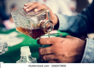 Hands pouring whiskey to a glass