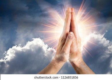hands in prayer with bright sunlight emenating from the clouds and hands