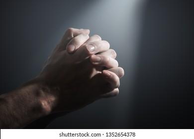 Hands of a prayer.  Light shining on praying man's hands.