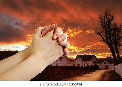 Hands praying with a dramatic red sky over a small town; prayer warrior.