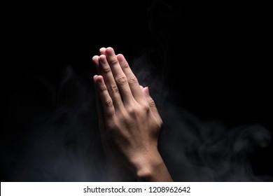 Hands with praying gesture over dark background. Christian Pray
