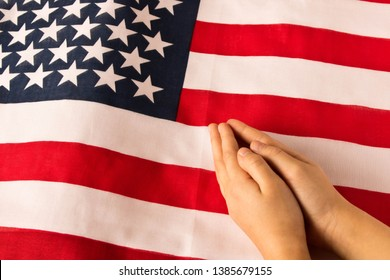 Hands of praying little girl on the background of the American flag. The concept of patriotism
