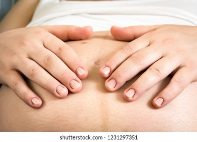 Hands of a pregnant woman caressing her belly. New life concept