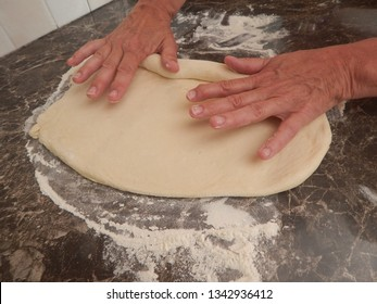 Hands prepare the pastry for a tart shell.