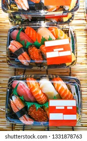 Hands are preparing Japanese sushi in a box.