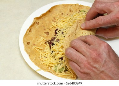 Hands preparing lunch of sun dried tomato soft wrap filled with beans, cheese and guacamole. Close-up of two male hands wrapping a vegetarian burrito on a plate
