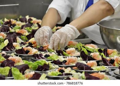 Hands preparing a shrimp salad at an industrial kitchen