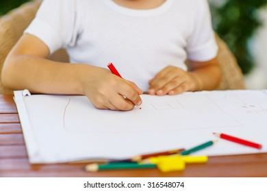 Hands of preschool kid boy  making homework. Little child painting with colorful pencils, indoors. School, education concept