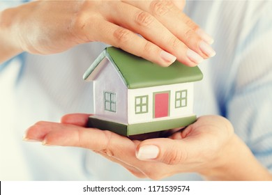 Hands presenting a small model of a