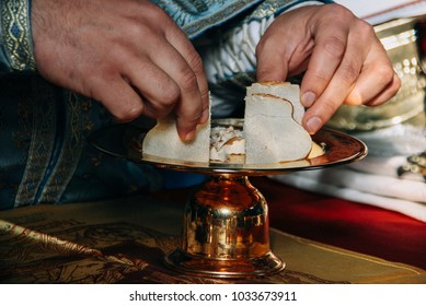 Hands of priest and orthodox prosphora for communion during holiday prayers in church. Shallow depth of field.