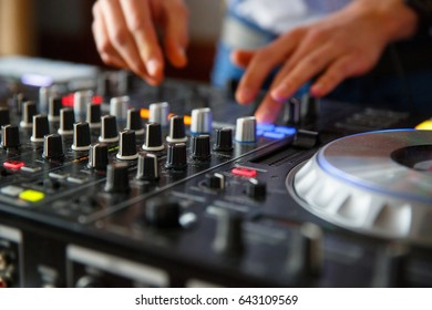 The hands of a professional DJ set up the dj's panel with a many buttons and control knobs to play music