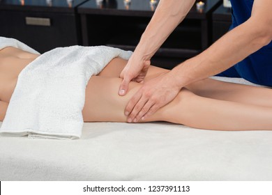 Hands of professional masseur massaging with hands quadriceps of female client lying on couch in spa cosmetology salon. Young woman caring about body and receiving healthy procedure.
