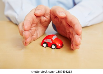 Hands protect a little red car as a symbol for car insurance