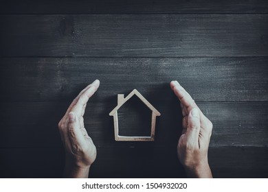 Hands protect wooden home on wood table background.  Property insurance and security concept.