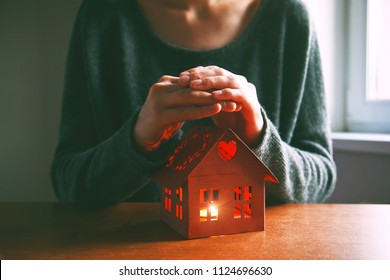 Hands protecting house with candle. Symbol of home safety and care