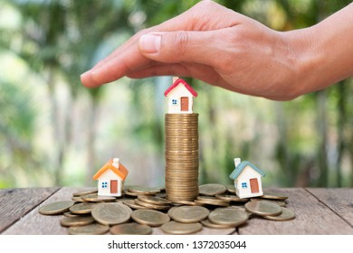 Hands as a protecting roof over a little house. Saving money for house and real estate. Woman hand protecting on  coins and house model on table.  House Model With Stacked Coins. Business growth.