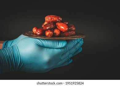 Hands in protective blue gloves hold a tray of dates. Celebrating Holy month Ramadan in quarantine. Epidemic, coronavirus pandemic or covid-19 concept