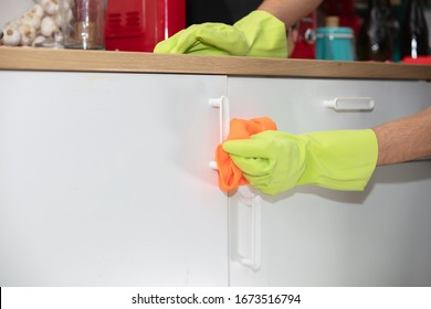 hands in protective gloves cleaning kitchen cabinet