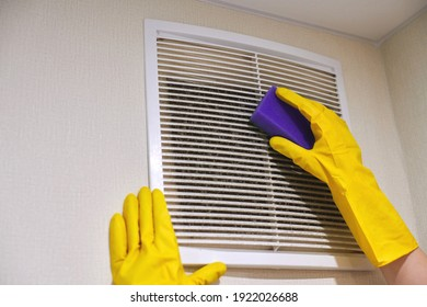 Hands in protective rubber gloves cleaning dusty air ventilation grill of HVAC. Cleaning service concept.