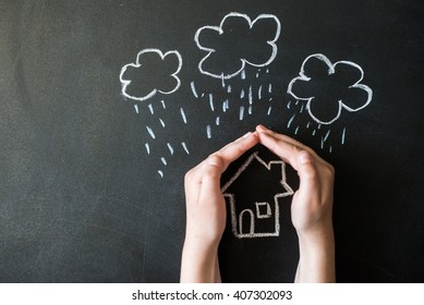 hands protects a house from the elements - rain or storm