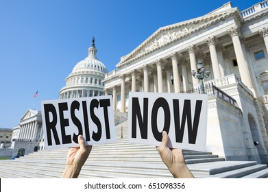 Hands of protesters in Washington, DC holding up signs urging their representatives on Capitol Hill to RESIST NOW, referring to the current political situation in the White House