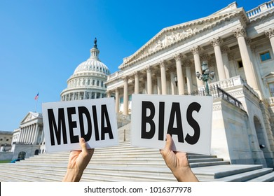 Hands of protestors holding up signs calling attention to media bias in Washington, DC, USA