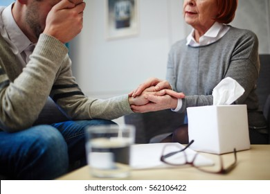 Hands of psychologist and despaired man over table with paper tissues