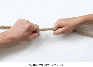 Hands pull a thick rope in different directions / tug of war