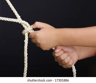 Hands pulling rope over dark background