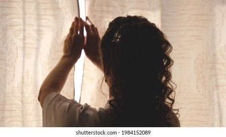 Hands pulling a window curtain for warm morning light. Slow motion. Young woman opening curtains in a bedroom. Closeup. Femele hands open window curtain in morning