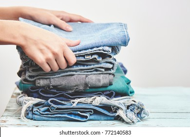 Hands, put the stack of blue jeans on white backgroundHands, put the stack of blue jeans on white background