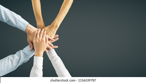 Hands put together on black background with copy space. Union, togetherness and teamwork concept