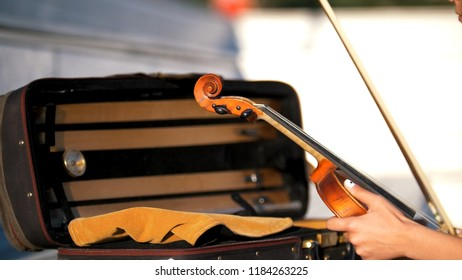 The hands put the violin in the case