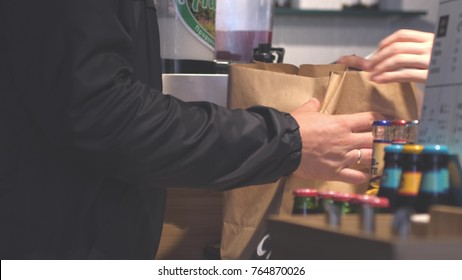 Hands putting burgers into bag. Man buys packaged food in cafe.