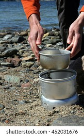 Hands putting down a kettle on a camping stove