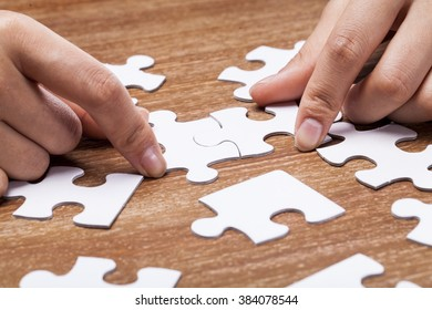 Hands putting puzzles together on desk.