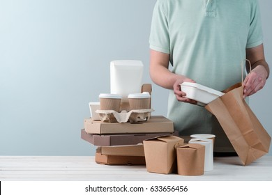 Hands putting take-out food container into paper bag, close-up. Coffee cups in holder, several pizzas, light grey background, place to insert your text. Food delivery.